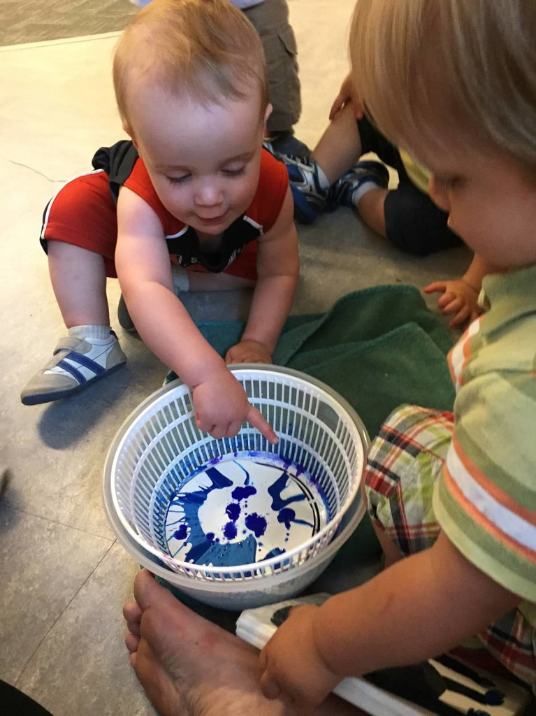 Infants spin paint in a salad spinner.